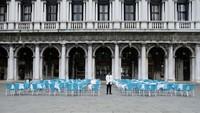 Namun sekarang, Italia dilockdown. Tampak seorang pelayan di Venesia sedang menanti tamu restoran, tapi tak ada seorang pun yang datang, padahal kursi-kursi sudah tertata rapi (Reuters)