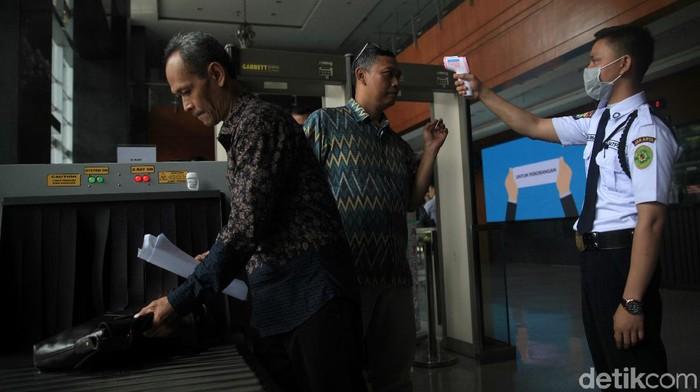 Para pengunjung dan petugas di Pengadilan Negeri Jakarta Pusat diperiksa suhu tubuhnya saat akan memasuki gedung. Hal itu dilakukan guna cegah penyebaran corona