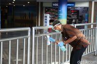 Petugas Mengelap Bagian-bagian Mudah Disentuh di Bandara Ngurah Rai