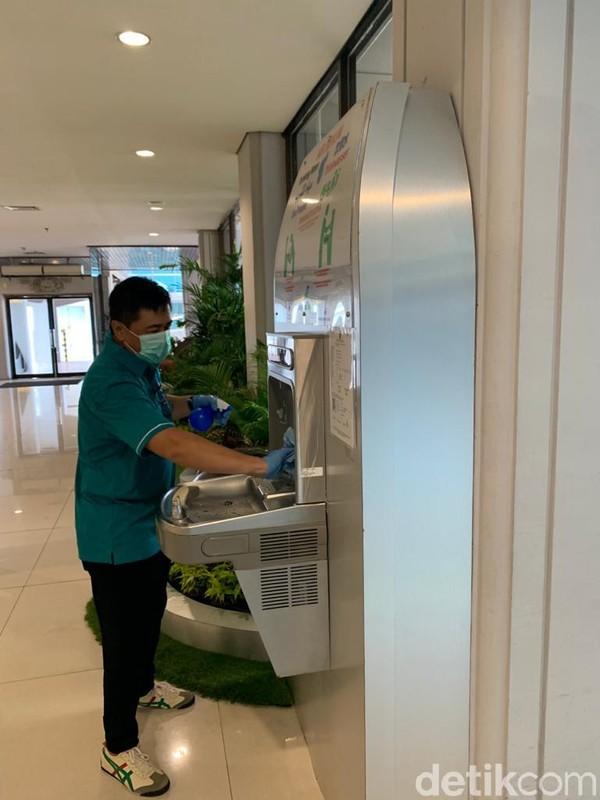 Kewaspadaan terhadap virus Corona di Bandara I Gusti Ngurah Rai Bali, terus digencarkan. Terlihat petugas mengelap area mesin isi ulang air mineral(Foto: Angga Riza/detikcom)