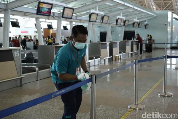 Ini merupakan bentuk komitmen pengelola Bandara Ngurah Rai untuk mengantisipasi adanya penularan virus Corona. Petugas mengelap tali pembatas di area check in (Foto: Angga Riza/detikcom)