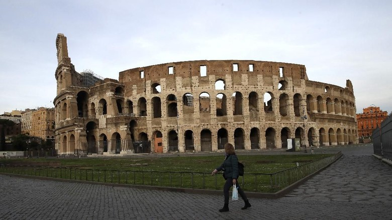 A woman walks in front of Romes ancient Colosseum in the afternoon of Thursday, March 12, 2020. A sweeping lockdown is in place in Italy to try to prevent it from becoming the next epicenter of the coronavirus epidemic. For most people, the new coronavirus causes only mild or moderate symptoms. For some, it can cause more severe illness, especially in older adults and people with existing health problems. (AP Photo/Alessandra Tarantino)