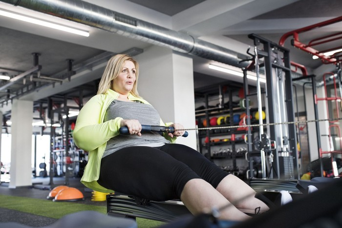 Attractive overweight woman in modern gym exercising on rowing machine. Chubby young blonde woman at fitness center.
