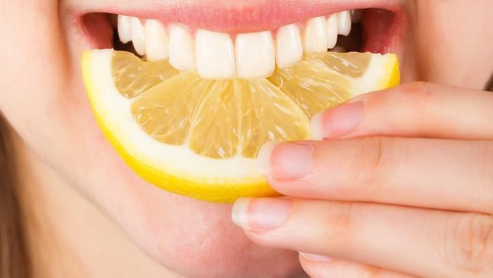 Close-up of a woman tasting sour lemon and smiling.