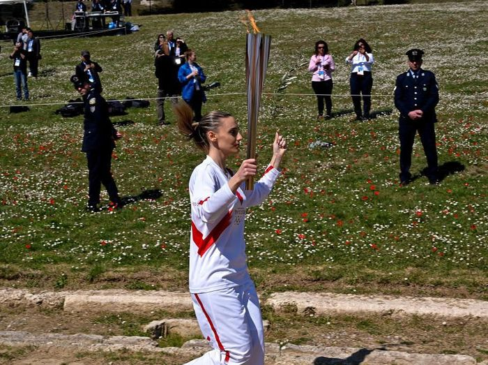 ATHENS, GREECE - MARCH 12:  Torchbearer Greeces Anna Korakaki, Rio 2016 gold medallist in the 25m pistol shooting,  past empty stadium as she holds the Olympic flame and an olive branch during the flame lighting ceremony on March 12, 2020 in ancient Olympia, ahead of the Tokyo 2020 Olympic Games . (Photo by Milos Bicanski/Getty Images)