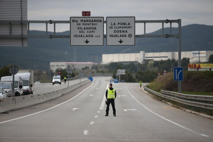 A mosso de esquadra police officer stands on the closed off road near Igualada, Spain, Friday, March 13, 2020. Over 60,000 people awoke Friday in four towns near Barcelona confined to their homes and with police blocking roads. The order by regional authorities in Catalonia is Spains first mandatory lockdown as COVID-19 coronavirus infections increase sharply, putting a strain on health services and pressure on the government for more action.  (AP Photo/Joan Mateu)