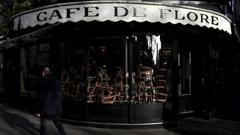 A picture taken on March 15, 2020 in Paris Saint-Germain-des-Pres district shows chairs piled up inside the Cafe de Flore as cafes and restaurants are closed amid spread of novel coronavirus (COVID-19). - France on March 14, 2020 drastically stepped up its measures against the spread of the coronavirus, announcing the closure of all non-essential public places including restaurants and cafes. (Photo by Philippe LOPEZ / AFP)