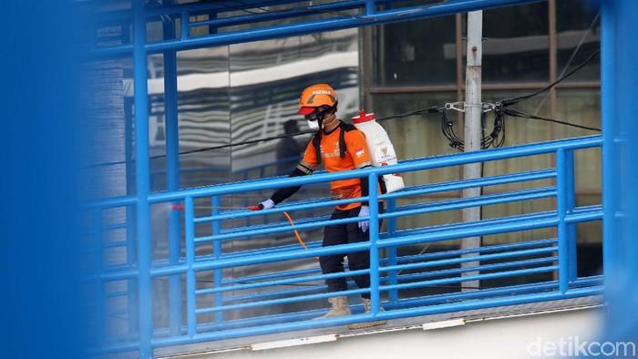Penyemprotan disinfektan dilakukan sebagai upaya cegah penyebaran corona. Area ruang publik seperti halte bus TransJakarta jadi sasaran penyemprotan disinfektan