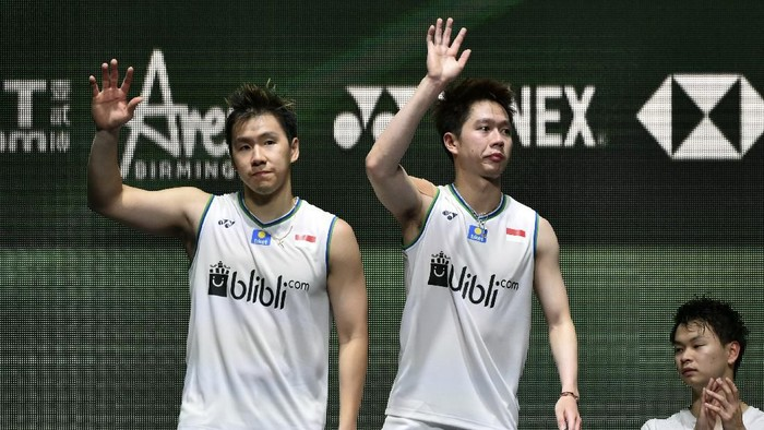 Marcus Fernaldi Gideon, left, and Kevin Sanjaya Sukamuljo of Indonesiaand wave from the podium after loosing to Yuta Watanabe and Hiroyuki Endo of Japan in the Mens Doubles final match at the All England Open Badminton tournament in Birmingham, England, Sunday, March 15, 2020. The Japanese team won 2-1. (AP Photo/Rui Vieira)