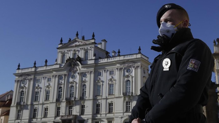 Policeman wearing a facemask stands on guard in front of closed Prague Castle, Czech Republic, Saturday, March 14, 2020. The Czech Republics government has approved further dramatic measures early Saturday to try and stem the spread of the coronavirus. The government has ordered retail businesses including shopping malls to close as of Saturday morning. For most people, the new coronavirus causes only mild or moderate symptoms. For some it can cause more severe illness. (AP Photo/Petr David Josek)
