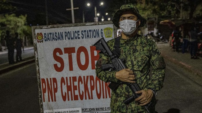 QUEZON, PHILIPPINES - MARCH 15: A police officer checks the temperature of a motorist at a checkpoint as authorities begin implementing a lockdown on Manila on March 15, 2020 in the outskirts of Metro Manila, Philippines. The Philippine government is placing some 12 million people in the capital Manila on lockdown as well as suspending government work for a month to prevent the spread of COVID-19. As of Saturday evening, the Philippines Department of Health has confirmed 111 cases of the deadly coronavirus in the country, with at least 8 recorded fatalities. (Photo by Ezra Acayan/Getty Images)