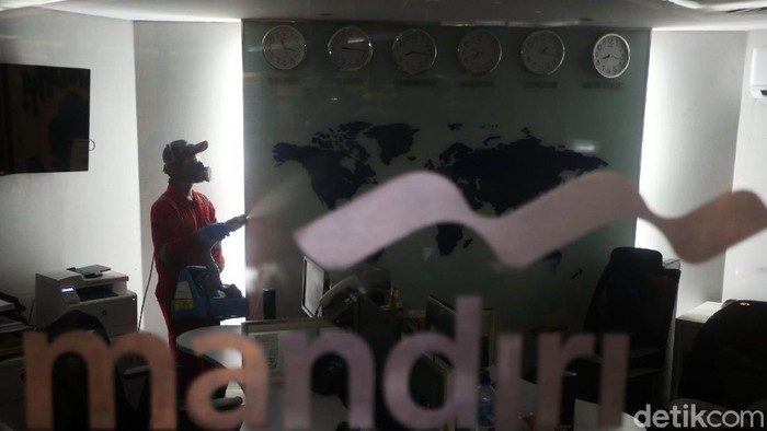 Petugas melalukan penyemprotan disinfektan di Kantor Bank Mandiri Cabang Thamrin, Jakarta, Senin (16/3/2020). Penyemprotan ini dilakulan guna mencegah penyebaran virus corona.