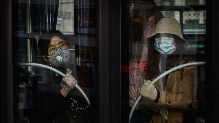 BEIJING, CHINA - MARCH 12: Chinese women wear protective masks as they ride the bus in the central business district  on March 12, 2020 in Beijing, China. The number of cases of the deadly new coronavirus COVID-19 being treated in China dropped to below 15,000 in mainland China Thursday, in what the World Health Organization (WHO) declared a global public health emergency last month. China continued to lock down the city of Wuhan, the epicentre of the virus, in an effort to contain the spread of the pneumonia-like disease but has moved to ease restrictions in other parts of the province. Officials in Beijing have put in place a mandatory 14 day quarantine for all people returning to the capital from other places in China and abroad. The number of those who have died from the virus in China climbed to over 3173 on Thursday, mostly in Hubei province, and cases have been reported in many other countries including the United States, Canada, Australia, Japan, South Korea, India, Iran, Italy, the United Kingdom, Germany, France and several others. The World Health Organization has warned all governments to be on alert and raised concerns over a possible pandemic. Some countries, including the United States, have put restrictions on Chinese travellers entering and advised their citizens against travel to China.(Photo by Kevin Frayer/Getty Images)
