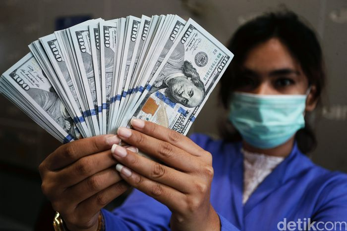 Petugas tengah menghitung mata uang Dolar AS, di VIP kawasan Cikini, Jakarta, Selasa (17/03/2020). Tekanan dari penyebaran wabah virus corona yang semakin meluas baik dalam skala global dan di dalam negeri turut mempengaruhi pelemahan rupiah.