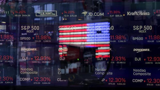 A United States flag is reflected in the window of the Nasdaq studio, which displays indices and stocks down, in Times Square, New York, Monday, March 16, 2020. (AP Photo/Seth Wenig)