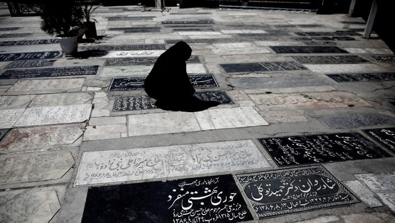 An Iranian woman visits a relatives grave at a cemetery in the religious Shiite city of Qom, some 130 kilometres south of the capital, on June 9, 2013. AFP PHOTO/BEHROUZ MEHRI (Photo by BEHROUZ MEHRI / AFP)