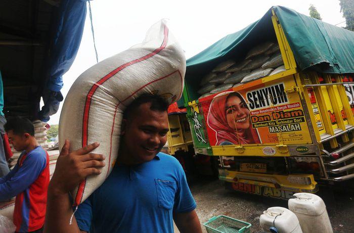 Pekerja melakulan aktivitas bongkar muat beras di Pasar Induk Beras Cipinang, Jakarta Timur, Rabu (18/3/2020).