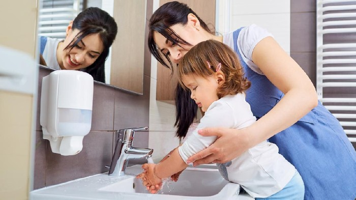 Portrait of a mother helping son wash his hand in the sink after making cookies – domestic life concepts