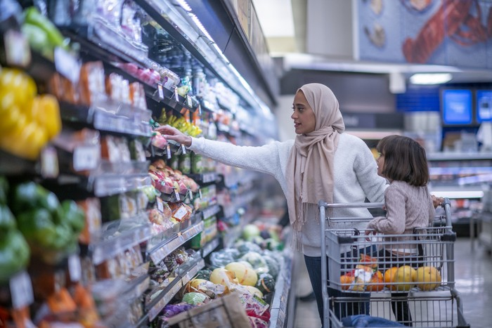 A young Muslim mother and daughter walk the produce aisles of the grocery store together shopping for groceries.  They are both dressed casually and the mother is wearing a Hijab.  The mother is reaching for products on the shelf while pushing a shopping cart with her daughter seated in it.