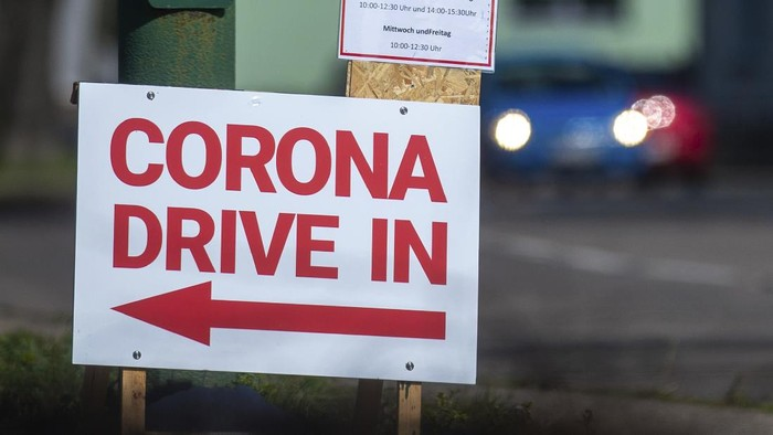 Corona Drive In can be read on a sign at an entrance to a parking lot in Schoenebeck, eastern Germany, Tuesday, March 17, 2020. Fever centres had been set up all over the country in the past few days. In Schoenebeck there is the possibility to drive with your own vehicle directly in front of a caravan. There you can get advice from a doctor and test yourself for Covid-19. Only for most people, the new coronavirus causes only mild or moderate symptoms, such as fever and cough. For some, especially older adults and people with existing health problems, it can cause more severe illness, including pneumonia. (Klaus-Dietmar Gabbert/dpa via AP)