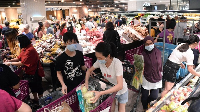 Shoppers looking at empty shelves at a supermarket in Kuala Lumpur, Malaysia, Tuesday, March 17, 2020. Malaysia has the highest number of cases in Southeast Asia and the fourth highest in Asia following a spike in recorded coronavirus cases after China, South Korea and Japan. For most people, the new coronavirus causes only mild or moderate symptoms. For some it can cause more severe illness. (AP Photo)