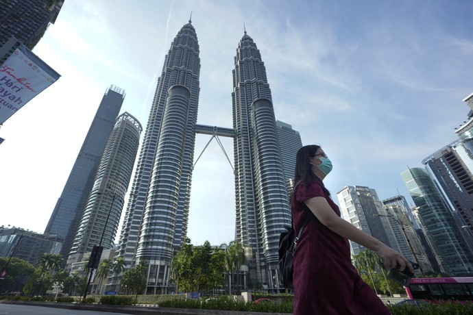 A girl wearing a face mask crossing a road in front of Twin Towers in Kuala Lumpur, Malaysia, Wednesday, March 18, 2020.  For most people the new COVID-19 coronavirus causes only mild or moderate symptoms, but for some it can cause more severe illness. (AP Photo/Vincent Thian)