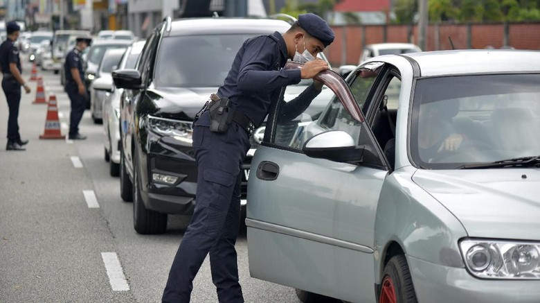 Police officers check vehicles at a roadblock to ensure that people abide by the movement control order in downtown Kuala Lumpur, Malaysia Thursday, March 19, 2020. Malaysian government issued a movement order to the public starting from March 18 until March 31 to block the spread of the new coronavirus. For most people the new coronavirus causes only mild or moderate symptoms, but for some it can cause more severe illness. (AP Photo)
