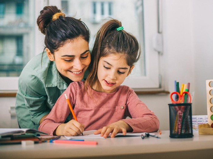 Happy family with kid playing together, caring mom and dad smiling teaching little daughter to draw with color pencils, mother and father having fun with cute child help in creative weekend activity
