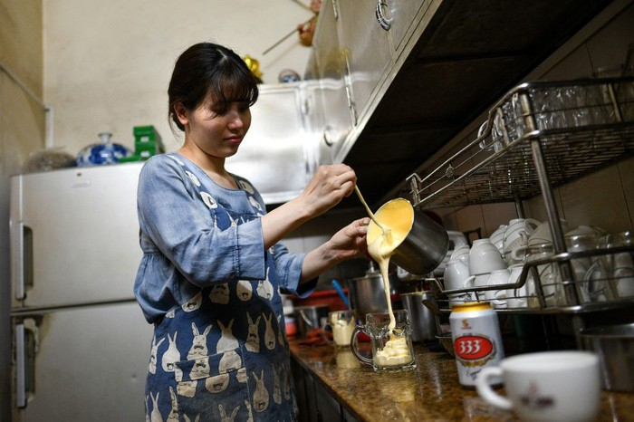 This picture taken on April 4, 2019 shows Nguyen Giang, daughter of Giang Cafe owner Nguyen Chi Hoa, pouring a sweetened egg mixture into a beer mug at the decades-old cafe in Hanoi. - Scrambled, fried, or ... whipped into beer? It might not be the most conventional way to serve eggs, but a decades-old Hanoi cafe is delighting drinkers with a frothy beer cocktail that has no place on a breakfast menu. (Photo by Manan VATSYAYANA / AFP) / TO GO WITH STORY VIETNAM-LIFESTYLE-BEVERAGE-BEER,FOCUS