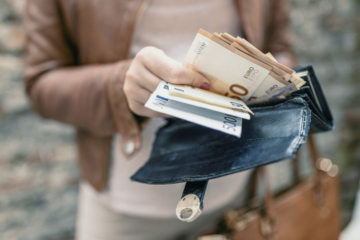 Woman holding in hands wallet with euro money. City girl is taking out money from wallet
