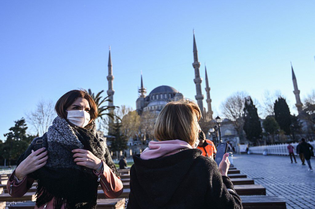 Women wear protective face masks near Sultanahmet Mosque also known as the Blue Mosque as the nation tries to contain the novel coronavirus, COVID-19, in Istanbul on March 17,2020. - Turkey on Monday suspended collective mosque prayers until further notice to limit the spread of the new coronavirus, while ordering the closure of public spaces including cinemas. The interior ministry later Monday said theatres, cinemas, concert halls, restaurants where there is live music, shisha cafes and places serving tea and coffee,night clubs,bars would be closed
