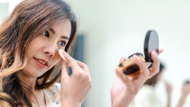 Portrait of Beautiful young Asian woman applying makeup, Attractive girl looking at mirror in pressed powder compact, holding make-up sponge. To cover face wrinkles, make skin smooth. Selective focus