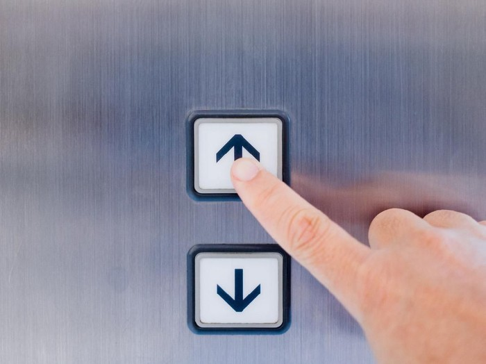 Hand pressing the button in the elevator in front view