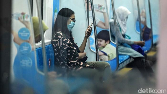 Para penumpang MRT Jakarta menggunakan moda transportasi umum tersebut dengan menjaga jarak sosial dari tanda silang yang dibuat oleh pengelola, di Jakarta, Jumat (20/3/2020). MRT Jakarta membuat tanda silang sebagai kursi yang tidak perlu diduduki di kursi kereta atau di peron ruang tunggu untuk membuat jarak sosial (social distancing) seperti yang disarankan pemerintah. Social Distancing untuk mencegah penyebaran virus Corona.