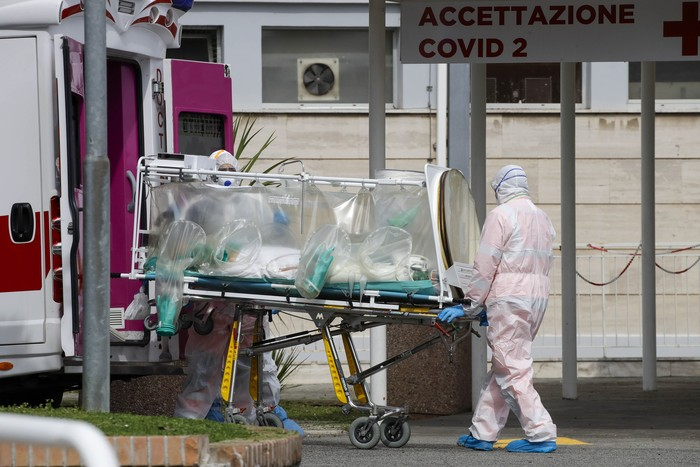 Two men stand outside the caravans they live in, in Rome, Wednesday, March 18, 2020. For most people, the new coronavirus causes only mild or moderate symptoms. For some it can cause more severe illness, especially in older adults and people with existing health problems.(AP Photo/Andrew Medichini)