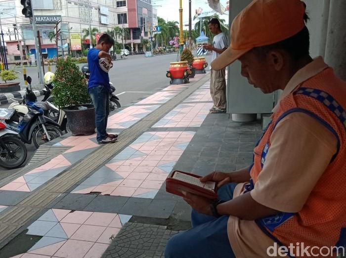 Sutarjo, juru parkir yang selalu mengaji di trotoar di sela pekerjaannya, Klaten, Jumat (20/3/2020).