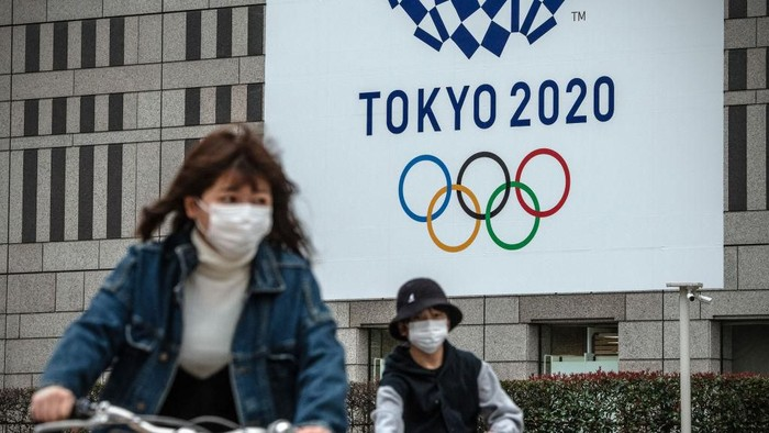 TOKYO, JAPAN - MARCH 13: People cycle past a banner for the Tokyo Olympics on March 13, 2020 in Tokyo, Japan. Excluding the Diamond Princess cruise ship cases, the number of coronavirus infections in Japan reached 684 today as United States President Donald Trump suggested the Tokyo Olympics should be postponed to next year. (Photo by Carl Court/Getty Images)