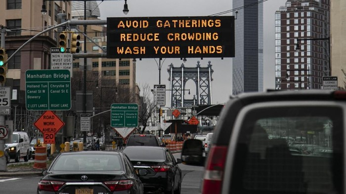 The Manhattan bridge is seen in the background of a flashing sign urging commuters to avoid gatherings, reduce crowding and to wash hands in the Brooklyn borough of New York, on Thursday, March 19, 2020. In a matter of days, millions of Americans have seen their lives upended by measures to curb the spread of the new coronavirus. For most people, the new coronavirus causes only mild or moderate symptoms. For some it can cause more severe illness. (AP Photo/Wong Maye-E)
