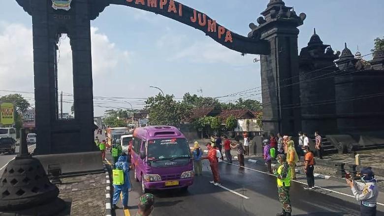 Petugas melakukan penyemprotan kendaraan yang melintasi di tugu perbatasan Jawa Tengah dan DIY di Salam, Magelang, Sabtu (21/3/2020).