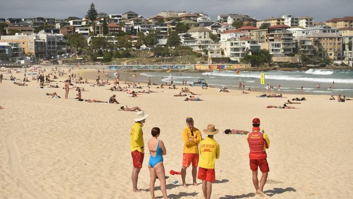 Surf Lifesavers ask people to leave Bondi Beach ahead of its closure in Sydney on March 21, 2020. - Authorities temporarily closed Bondi Beach on March 21, after huge crowds flocked to the iconic surfing spot despite government orders not to congregate due to the coronavirus pandemic. (Photo by PETER PARKS / AFP)