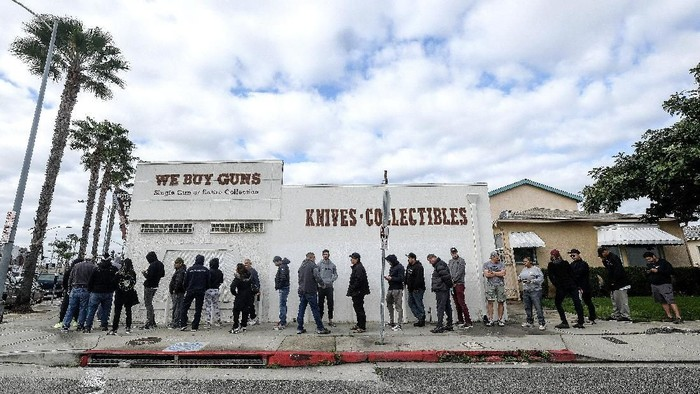People wait in a line to enter a gun store in Culver City, Calif., Sunday, March 15, 2020. Coronavirus concerns have led to consumer panic buying of grocery staples, and now gun stores are seeing a similar run on weapons and ammunition as panic intensifies. (AP Photo/Ringo H.W. Chiu)