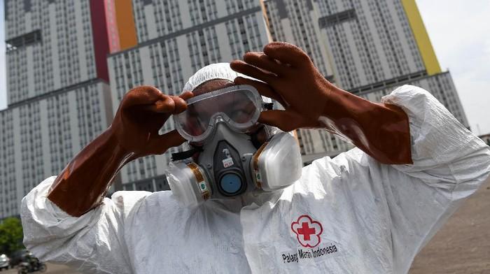 Petugas Palang Merah Indonesia (PMI) memakai kacamata pelindung untuk melakukan penyemprotan cairan disinfektan pada Wisma Atlet di Kemayoran, Jakarta, Sabtu (21/3/2020). Pemerintah menyiapkan Wisma Atlet Kemayoran sebagai rumah sakit darurat penanganan virus COVID-19 serta akan menjadi rumah isolasi bagi pasien yang rencannya akan digunakan pada hari ini, Sabtu (21/3/2020). ANTARA FOTO/M Risyal Hidayat/hp.