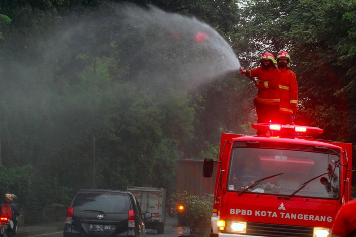 Petugas dari Dinas Pemadam Kebakaran dan BPBD Kota Tangerang dengan mobil pemadam melakukan penyemprotan cairan disinfektan terhadap ruang udara dan rambu lalulintas di Jalan Raya Daan Mogot, Tangerang, Banten, Jumat (20/3/2020). Penyemprotan dilakukan untuk meminimalisir penyebaran COVID-19 di ruang udara dan ruas jalan yang menghubungan dua provinsi yakni Jakarta dengan Banten. ANTARA FOTO/Muhammad Iqbal/foc.