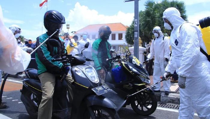 Sebagai salah satu pencegahan virus Corona, penyemprotan disinfektan terus dilakukan. Di Surabaya operasi disinfeksi menyasar para pengemudi ojol.