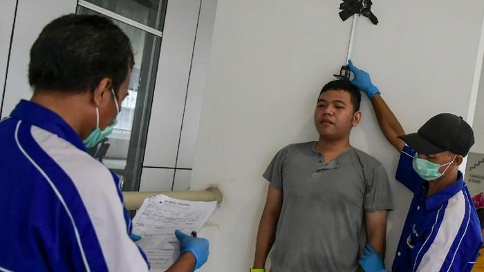 Sejumlah calon relawan mengantre untuk melakukan tes kesehatan di kompleks Wisma Atlet di Kemayoran, Jakarta, Minggu (22/3/2020). Kementerian BUMN mencari Relawan Gugus Tugas Penanganan Covid-19 yang memiliki tugas untuk membantu bidang logistik dan operasional penanganan Covid-19. ANTARA FOTO/Galih Pradipta/foc.