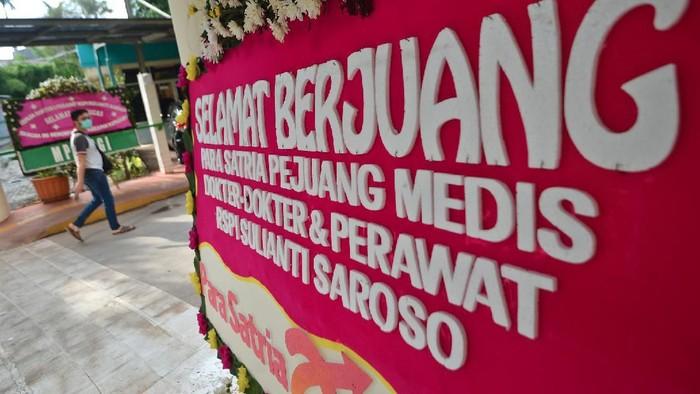 Warga berjalan di samping karangan bunga dukungan untuk tenaga medis dan staf Rumah Sakit Penyakit Infeksi (RSPI) Sulianti Saroso di Jakarta, Sabtu (21/3/2020). Puluhan kiriman karangan bunga dari masyarakat terpasang sejak Jumat (20/3) berisi doa untuk tenaga medis agar terus sehat selama menangani pasien terinfeksi COVID-19 di Indonesia. ANTARA FOTO/Aditya Pradana Putra/aww.