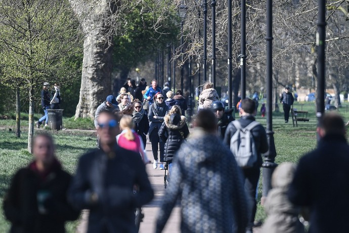 LONDON, ENGLAND  - MARCH 22: People are seen walking on Clapham Common on March 22, 2020 in London, United Kingdom. British Prime Minister Boris Johnson urged that people dont visit their parents this Mothering Sunday to curb the spread of COVID-19, which has killed 233 people in the UK.  (Photo by Peter Summers/Getty Images)
