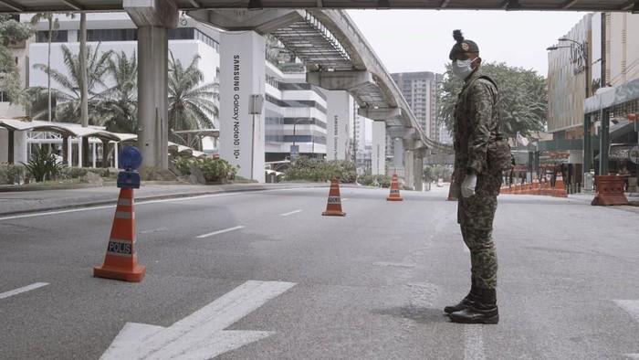 Ratusan polisi bersiaga di sejumlah kawasan Kuala Lumpur, Malaysia. Para polisi dikerahkan untuk menjaga kawasan yang kini tengah lockdown untuk cegah Corona.