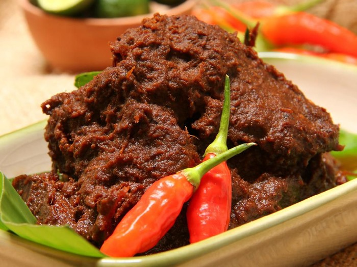 Rendang Padang, the most famous Padangnese dish of spicy dry beef stew. Plated on a rectangular ceramic plate that has been lined with banana leaf. Two chili peppers are used to garnish the dish.