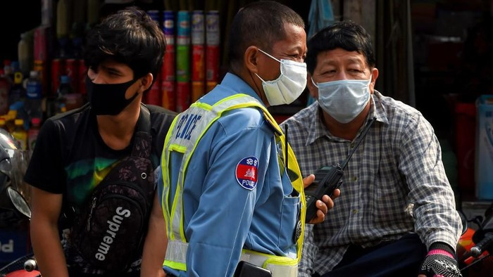 A policeman (C) and people wear facemasks, used as a preventive measure against the COVID-19 novel coronavirus, at a market in Phnom Penh on March 17, 2020. (Photo by TANG CHHIN Sothy / AFP)